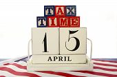 pic of year end sale  - USA Tax Day April 15 concept with vintage style calendar and Tax Time blocks on flag on blue wood background - JPG
