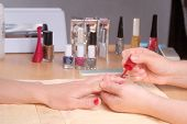 image of nail salon  - Manicurist doing manicure client painting nails with red nail polish in salon on yellow towel  - JPG