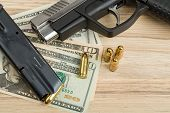 foto of corruption  - detail of gun with bullet on US dollar banknotes crime or corruption concept - JPG