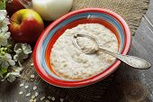 pic of porridge  - Porridge and red apples on a wooden table - JPG