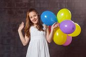 stock photo of ten years old  - Ten year old caucasian girl with long hair posing in the studio with balloons - JPG