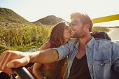 pic of road trip  - Woman kissing her boyfriend driving a car - JPG