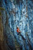 stock photo of climbing wall  - female rock climber climbs on a rocky wall  - JPG