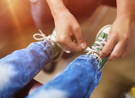 stock photo of passenger train  - Father tying shoe laces of his son traveling in train - JPG