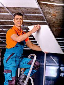 picture of suspenders  - Man in builder uniform installing suspended ceiling - JPG