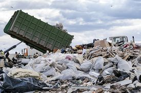 stock photo of dump_truck  - Garbage truck unloads garbage from container at the dump - JPG