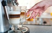 Glasses Fileed With Capuccino In Cofee Machine With Womans Hand