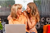 Daughter explaining internet to her mother at home, both women are sitting in front of a laptop PC