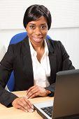 Happy Beautiful Black Woman Using Laptop In Office