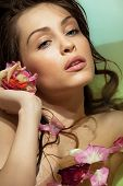 Beautiful woman relaxing in bath with rose petal. Body care.