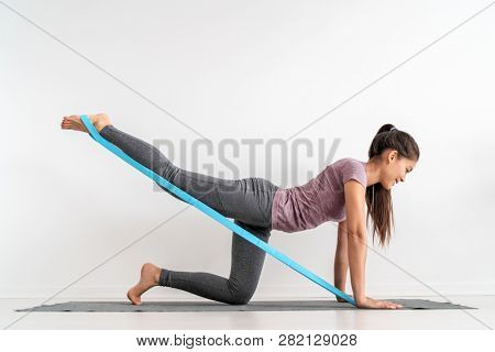 poster of Resistance band fitness girl doing leg workout donkey kick floor exercises with rubber strap elastic