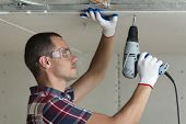 Young Man In Goggles Fixing Drywall Suspended Ceiling To Metal Frame Using Electrical Screwdriver On poster