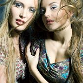 Fashiong Portrait Of Two Beautiful Women With Streaming Hair Looking In Camera