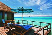 Overwater villa balcony overlooking green tropical lagoon