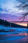 Icy Delaware River Reflects The Vivid Sunset Near Milford Bridge, Pa, Portrait poster