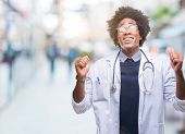 Afro american doctor man over isolated background smiling crossing fingers with hope and eyes closed poster