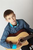 stock photo of 13 year old  - 13 year old teenage boy concentrating on playing acoustic guitar - JPG