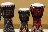 foto of congas  - Three wooden and decorated African bongos African art - JPG