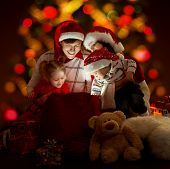 Happy Family Of Four Persons In Red Hats Opening Lighting Bag With Gifts