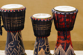 stock photo of congas  - Three wooden and decorated African bongos African art - JPG