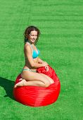Beautiful girl sits on a soft red pufe on the green grass