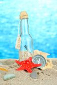 Glass of bottle with note inside on bright blue background