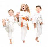 Three cheerful girl dressed in a white kimono kick leg