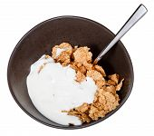Yoghurt And Spoon Into Bowl Of Cereal