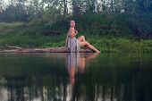 Pretty Girl In Cotton Dress Is Sitting On The Log