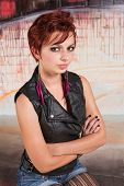 picture of headstrong  - Frowning young woman sitting with folded arms - JPG