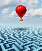 stock photo of balloon  - Rise above the challenges of business and life concept with a red hot air balloon with a businessman inside flying over a confusing maze or labyrinth puzzle as a metaphor for conquering adversity success with leadership - JPG