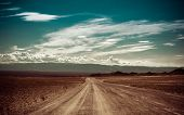 Empty Rural Road Going Through Prairie Under Cloudy Sky In Charyn Canyon
