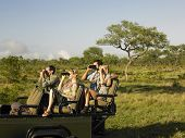 Group of tourists sitting in jeep and looking through binoculars