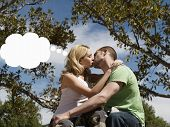 Side view of a young couple kissing with thought bubble above woman's head outdoors