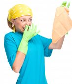 Young woman as a cleaning maid holding rag and pinching her nose because of bad smell, isolated over white