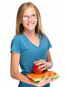 Young skinny student girl is holding exercise books and apple, isolated over white