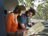 picture of campervan  - Happy young couple looking at map sitting in open campervan - JPG