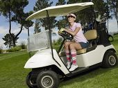 Cheerful female golfer driving golf cart in course