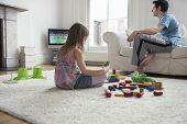 Girl sitting on floor and playing with blocks while father watching television at home