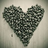 a pile of roasted coffee beans forming a heart, on a wooden table , in black and white