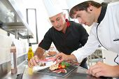 Chef helping student in catering to prepare foie gras dish