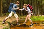 image of woman boots  - Hiker boy help trekking girl crossing the creek - JPG