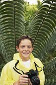 Portrait of happy young boy with camera by large fern in forest during field trip