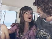 picture of campervan  - Smiling young couple looking at each other in campervan - JPG