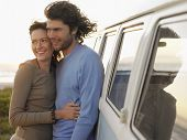 image of campervan  - Loving young couple embracing by campervan on beach - JPG