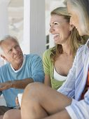 Hombre maduro con dos mujeres de mediana edad, sentado en la terraza