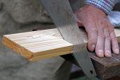Wood Workshop. Carpenter Cutting Plank With Hand Saw