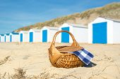 Row blue and white beach cabins and picmic basket with checked napkin