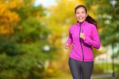 Female jogger. Fit young Asian woman jogging in park smiling happy running and enjoying a healthy ou