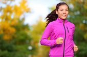 Running woman jogging in autumn forest in fall. Beautiful female runner wearing autumn running jacke